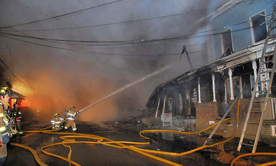 Firefighters battle a blaze that destroyed as many as eight homes in the 500 block of Howard Street in Frackville Sunday morning.